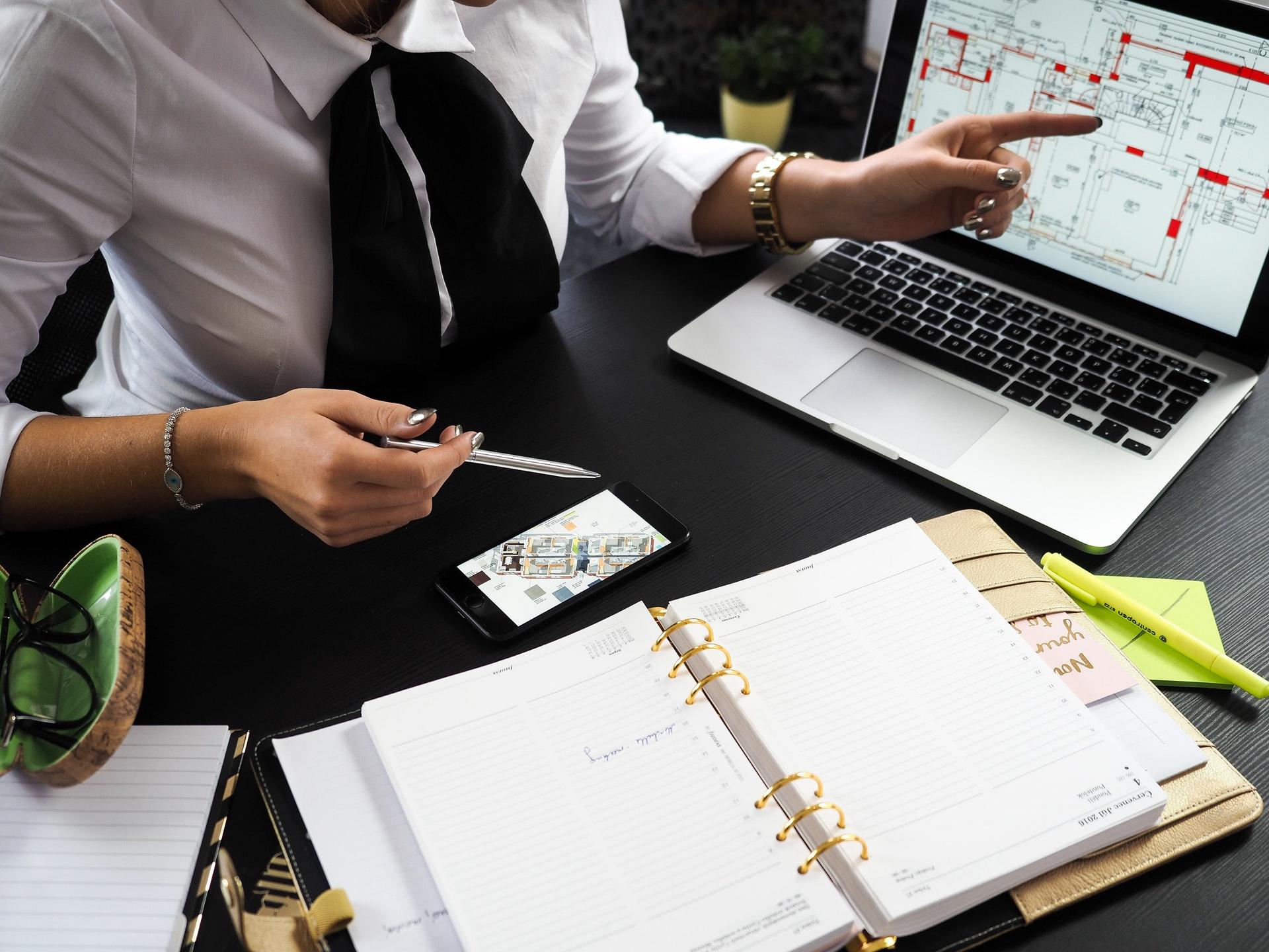 Profissional do mercado imobiliário fazendo análises. Há cadernos sobre uma mesa preta e um notebook, no qual se vê a planta de uma contrução.