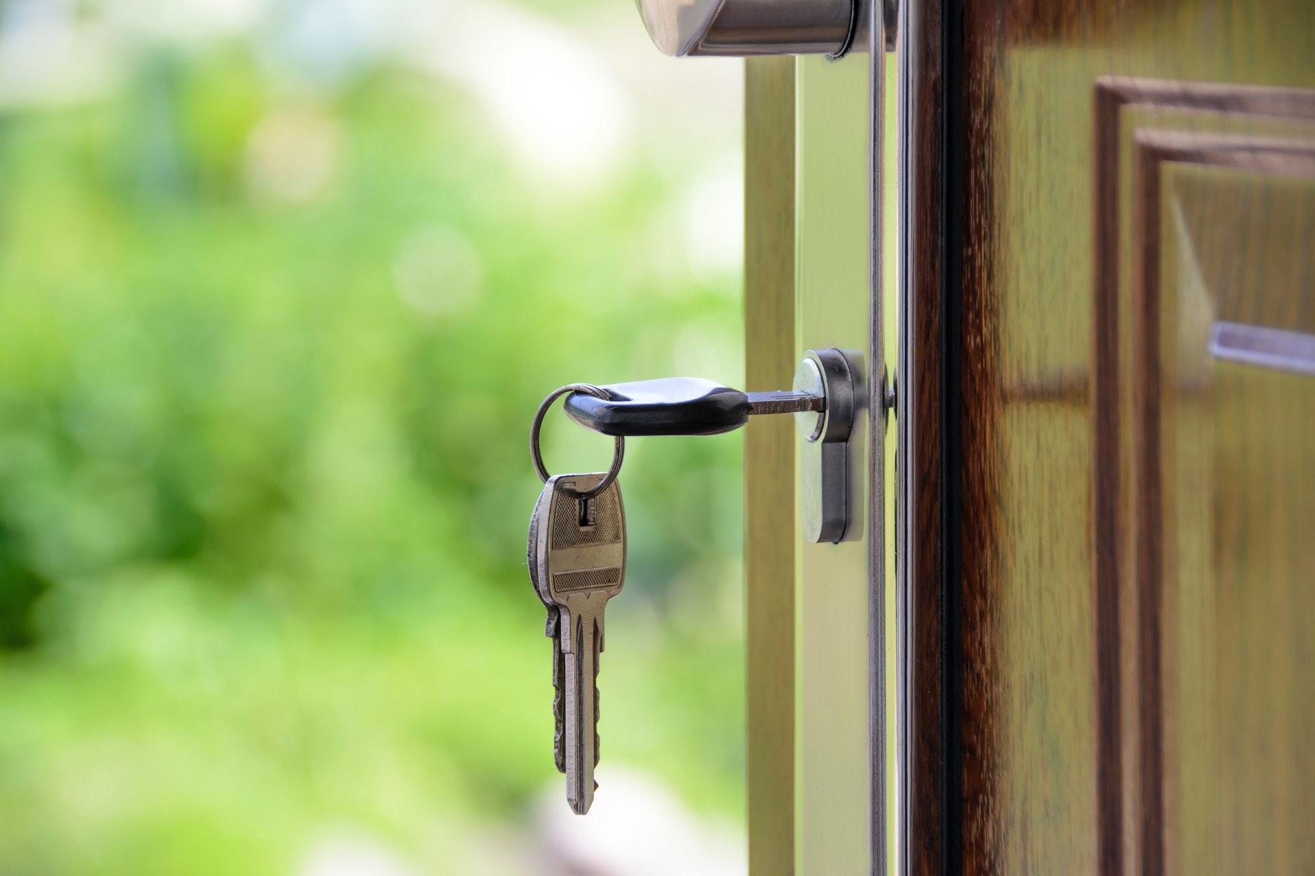 Destaque de uma chave inserida em uma porta de madeira. Ao fundo, vegetação.